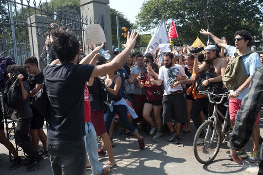 Students and National Museum personnel break past a police barrier to protest on the property of the museum which suffered an overnight fire in Rio de Janeiro.