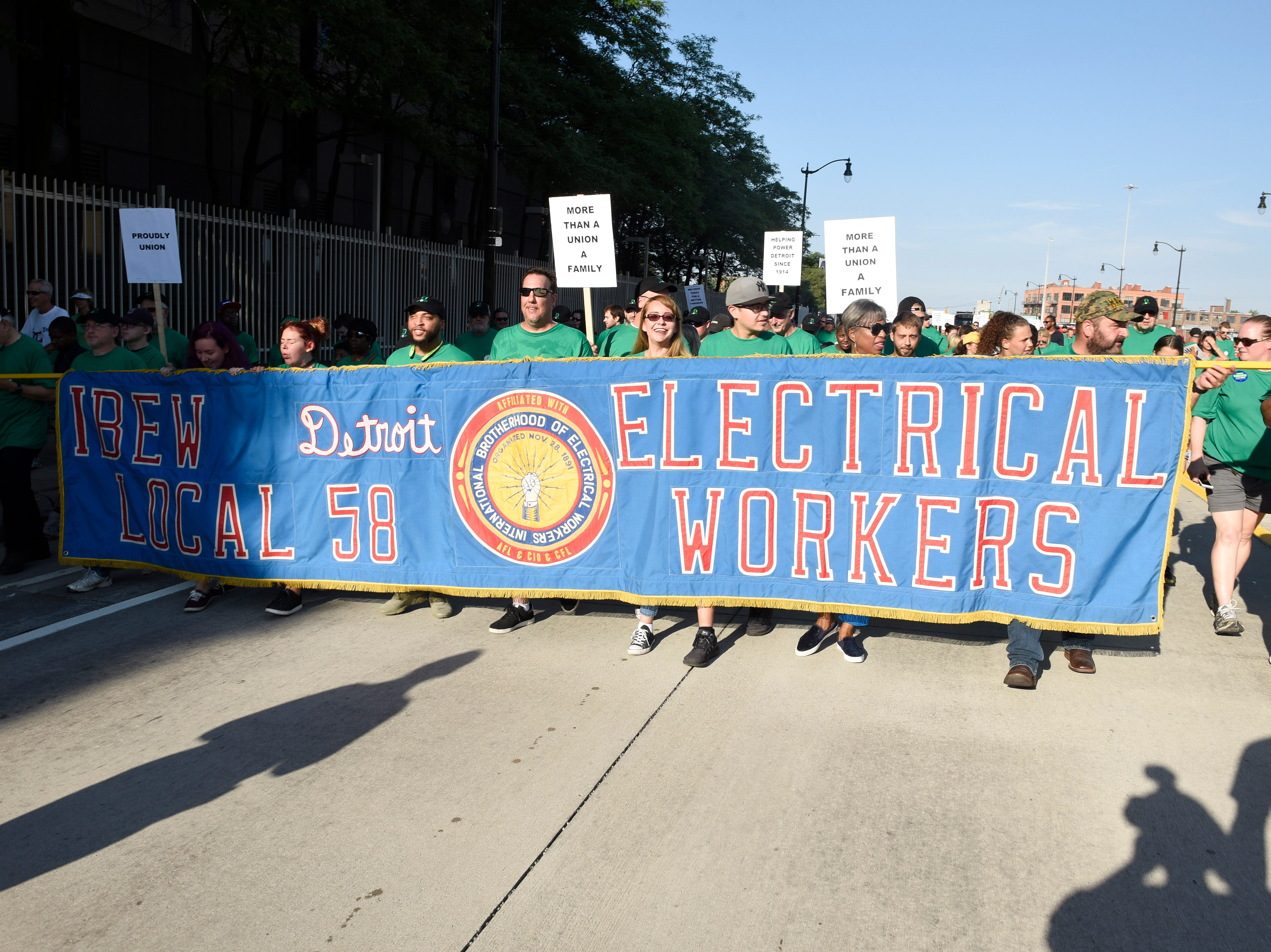 International Brotherhood of Electrical Workers Local 58 electrical workers walk the parade route along Michigan Ave.to Hart Plaza.