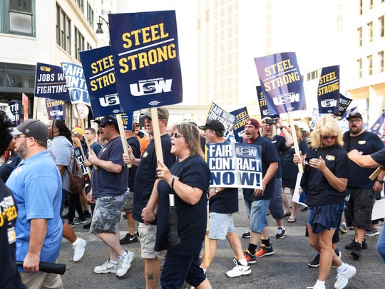 Members of the United Steel Workers union walk the parade route along.