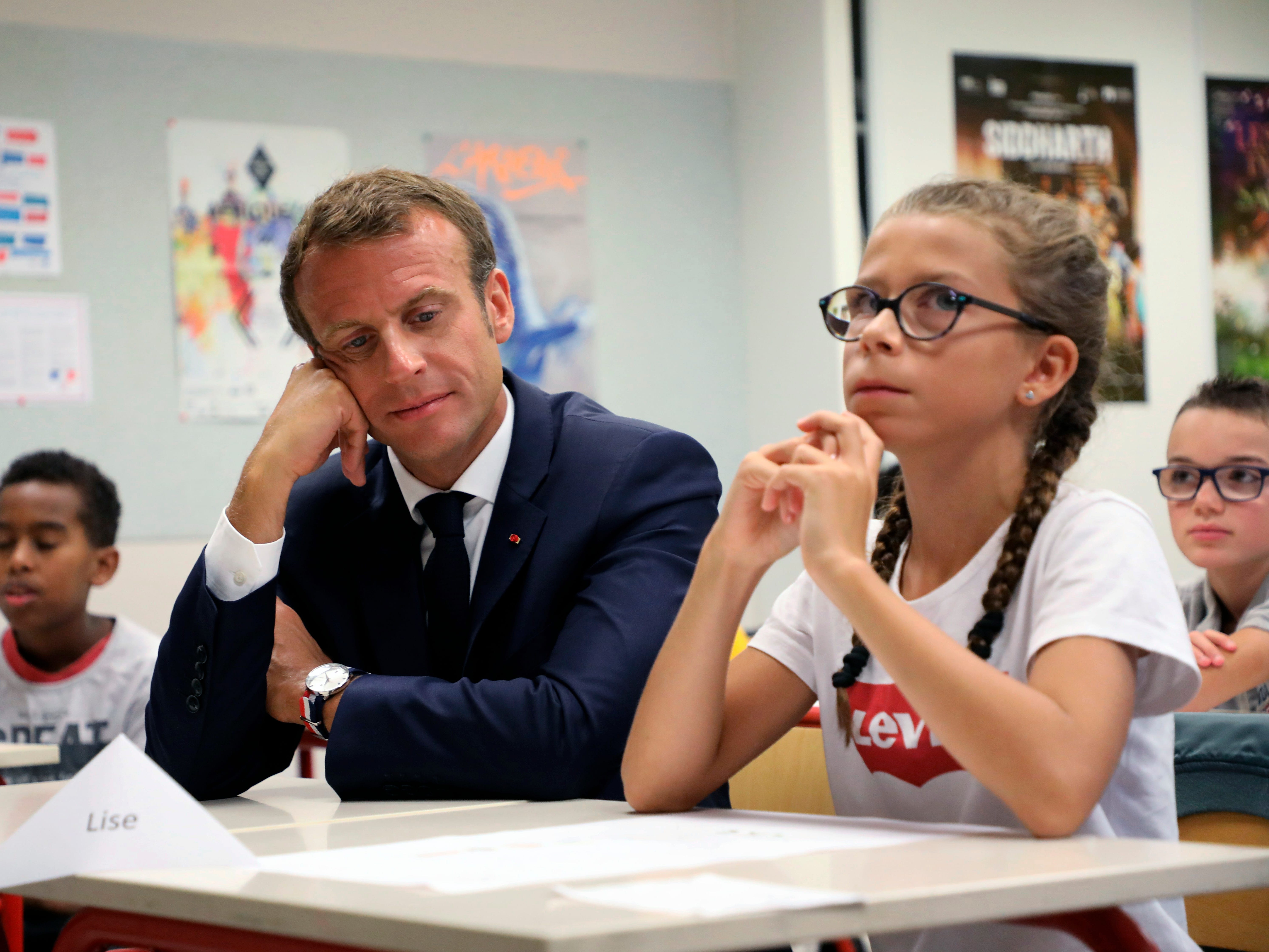 French president Emmanuel Macron, left, sits next to a pupil in a classroom during his visit in a secondary school in Laval, western France, Monday, Sept. 3, 2018, at the start of the school year in France.