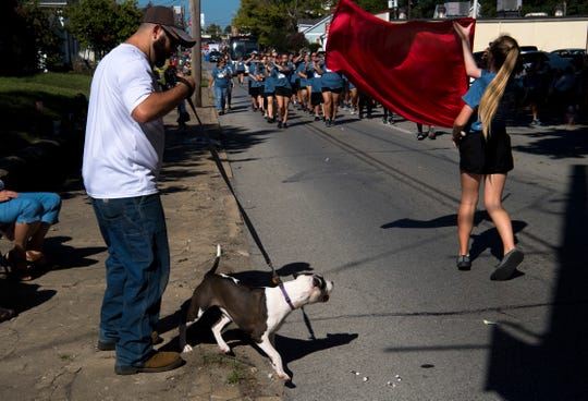Dakota Ballis of Boonville, Ind., tries to keep his 7 month old pup, Genny, from playing with the flag twirlers in the Princeton High School Band during the 132nd Annual Labor Day Celebration in Boonville, Ind., Monday morning.