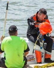 Chris Ritz (right) slowly climbs out of his boat after nearly flipping during the National Modified final. It was stopped for safety reasons and later re-started.