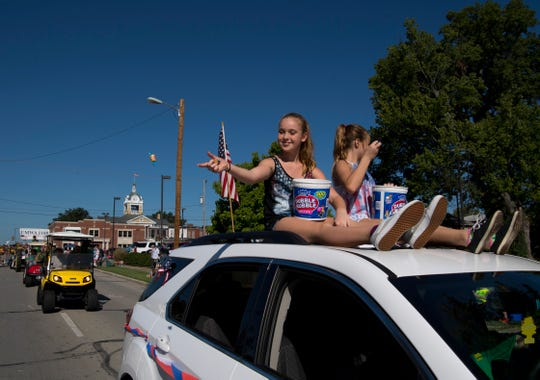 MaKayla McCool, 11, left, and Eva Bond, 11, both from Evansville, toss Dubble Bubble bubble gum to kids while representing Local 1907 at the 132nd Annual Labor Day Celebration in Boonville, Ind., Monday morning.