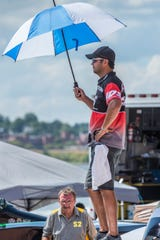 Tom Bergman of Evansville tries to create some shade as he watches a heat from the pits during the 2018 HydroFest.