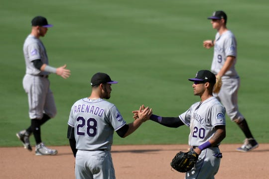 Colorado Rockies third baseman Nolan Arenado and first baseman Ian Desmond congratulate one another after a win in San Diego last season. Desmond may be moving from first base to center field this season.