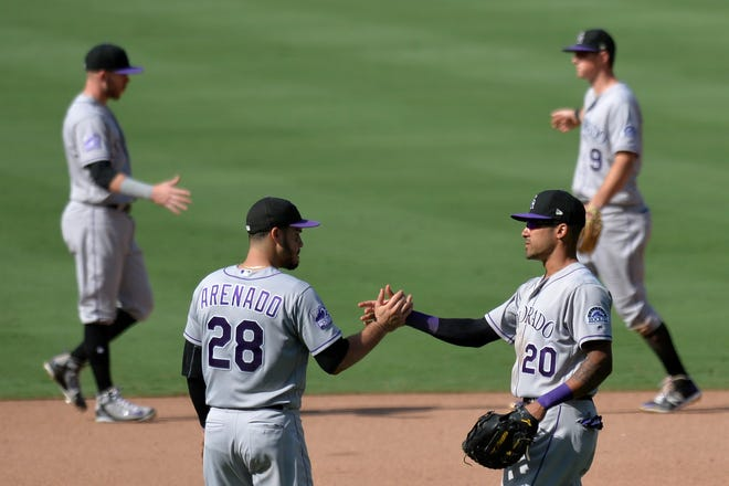 Colorado Rockies third baseman Nolan Arenado (28) and first baseman Ian Desmond (20) congratulate one another after a win Sunday in San Diego. The Rockies returned home Monday and will play the second of 10 straight home games at 6:40 p.m. Tuesday against the San Francisco Giants at Coors Field.