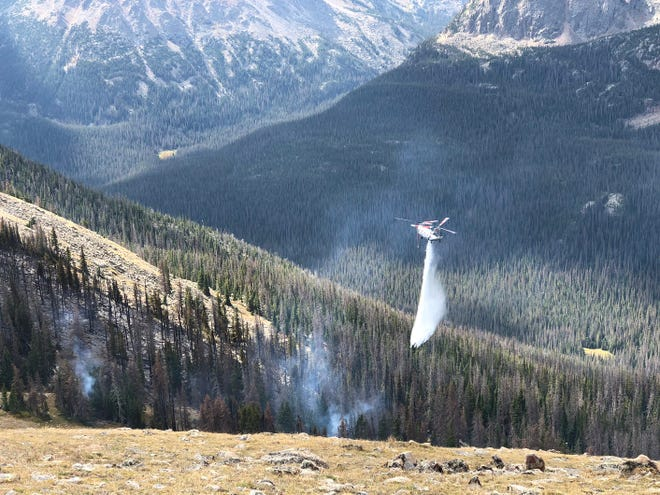 A helicopter drops water on the Forest Canyon Fire at Rocky Mountain National Park.