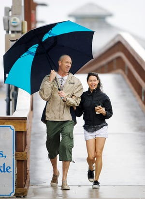 Rain from Tropical Storm Gordon or red tide concerns didn't stop Brian and Sherie Stevens from enjoying a Labor Day walk Monday on Fort Myers Beach.