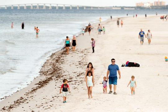 Jason Carter and his family, bottom front, were among several beachgoers enjoying Labor Day on Monday on Fort Myers Beach.