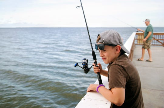 Paul Gorenyuk, 9, spends Labor Day fishing with his father, Ed, right, on Monday on Fort Myers Beach.