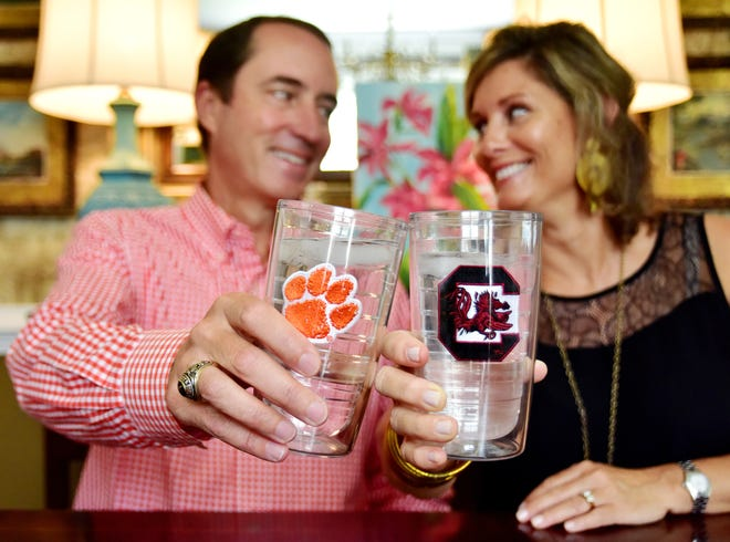William and Laura Lynn Luce cheers with cups with Clemson and USC logos.
