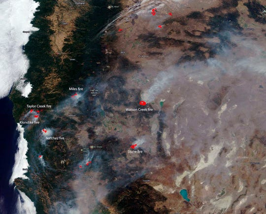 This NASA satellite image posted Aug. 20, 2018 shows several of the larger wildfires in both Oregon, top, and California. Wildfires in the U.S. have charred more than 10,000 square miles so far this year, an area larger than the state of Maryland, with large fires still burning in every Western state including many that are not fully contained. Whether sparked by lightning or humans, fire has long been a force shaping the landscape of the U.S. West. (NASA via AP)