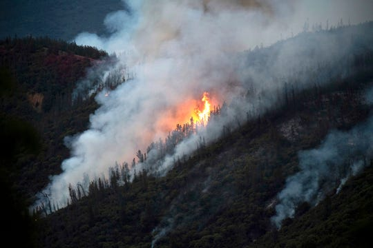 FILE - In this Sunday, July 15, 2018, file photo, flames from the Ferguson fire burn down a hillside in unincorporated Mariposa County Calif., near Yosemite National Park. Wildfires in the U.S. have charred more than 10,000 square miles so far this year, an area larger than the state of Maryland, with large fires still burning in every Western state including many that are not fully contained. Hot, dry winds can whip flames into firestorms that leave behind charred wastelands prone to erosion and mudslides. (AP Photo/Noah Berger, File)