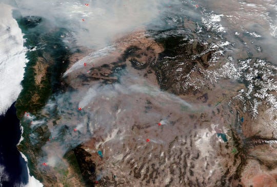 This image posted by the National Oceanic and Atmospheric Administration (NOAA), released by NASA, on Aug. 20, 2018, shows Western states, California at left, shrouded in smoke from the more than 100 large fires, including smaller fires within each complex of fires, that have erupted across the region during this fire season. Wildfires in the U.S. have charred more than 10,000 square miles so far this year, an area larger than the state of Maryland, with large fires still burning in every Western state including many that are not fully contained. Whether sparked by lightning or humans, fire has long been a force shaping the landscape of the U.S. West. (NOAA via AP)