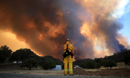 FILE - In this Aug. 2, 2018, file photo, a tower of smoke pours from Cow Mountain as Burney, Calif., firefighter Bob May keeps a watch on surrounding vegetation for spot fires during the River wildfire near Lakeport, Calif. Wildfires that have long shaped the landscape of the U.S. West are getting bigger and burning longer – bringing more choking smoke, deadly mudslides and habitat loss. (Kent Porter/The Press Democrat via AP, File)