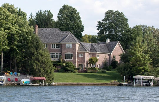 The home of John Krull, which sits adjacent to a deck and wall (bottom left), built by neighbor Ray Peck on his property, Indianapolis, Wednesday, Aug. 22, 2018. Peck says that he is being unfairly targeted by the city of Indianapolis after building a 25 foot structure on his property where it faces Geist Reservoir.