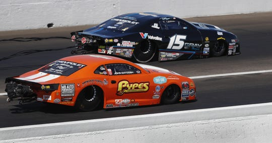Pro Stock driver Tanner Gray, right, drives by John Gaydosh, left, during the NHRA U.S. Nationals at Lucas Oil Raceway on Sunday, Sept. 3, 2018.