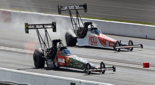 Top Fuel driver Terry McMillen, left, drives by Blake Alexander during the NHRA U.S. Nationals at Lucas Oil Raceway on Monday, Sept. 3, 2018.