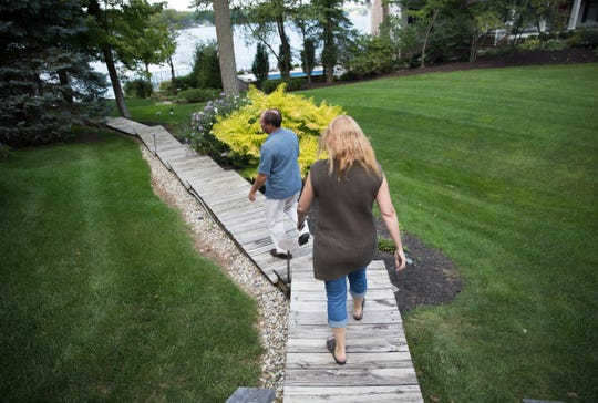 Ray Peck and his wife Kim Peck walk on their property, Indianapolis, Wednesday, Aug. 22, 2018. Peck says that he is being unfairly targeted by the city of Indianapolis after building a 25 foot structure on his property where it faces Geist Reservoir.