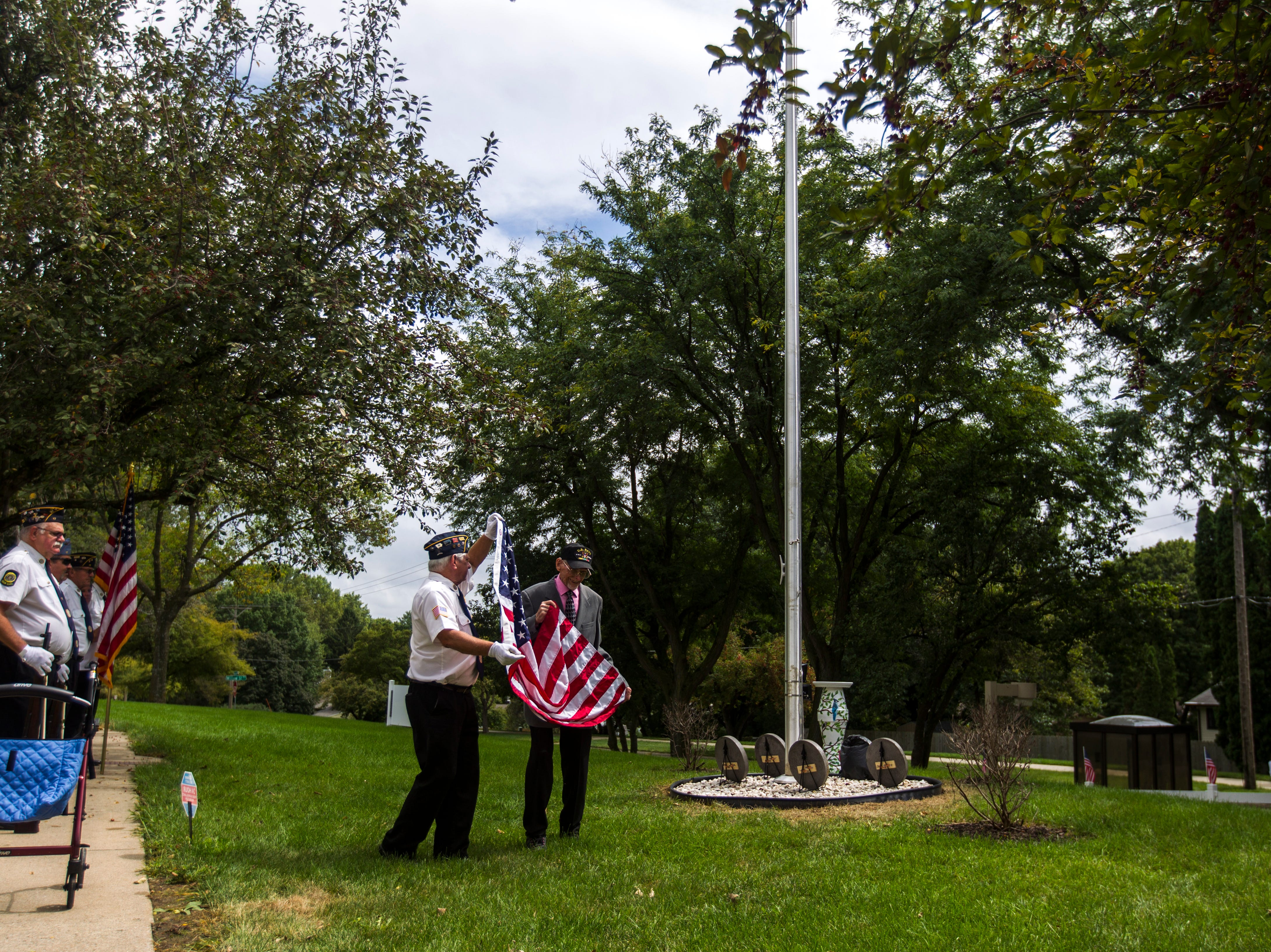 World War II U.S. Navy veteran Russell H. Ware (left) helps American Legion Post 721 honor guard Sgt. of arms Tom Travis raise a flag during a dedication ceremony on Monday, Sept. 3, 2018, at the Autumn Park Apartments in Iowa City.