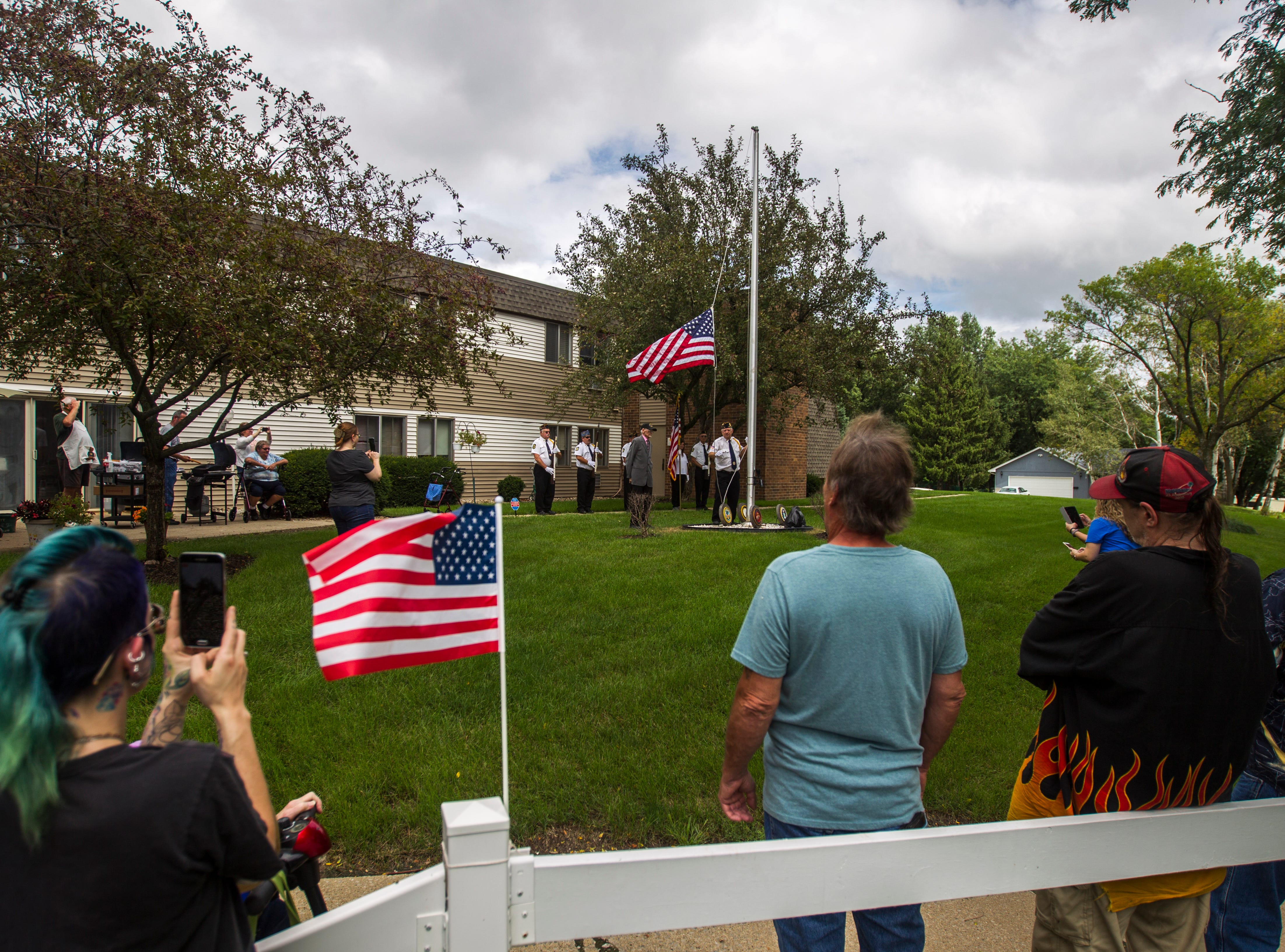 World War II U.S. Navy veteran Russell H. Ware watches American Legion Post 721 honor guard Sgt. of arms Tom Travis raise a flag during a dedication ceremony on Monday, Sept. 3, 2018, at the Autumn Park Apartments in Iowa City.