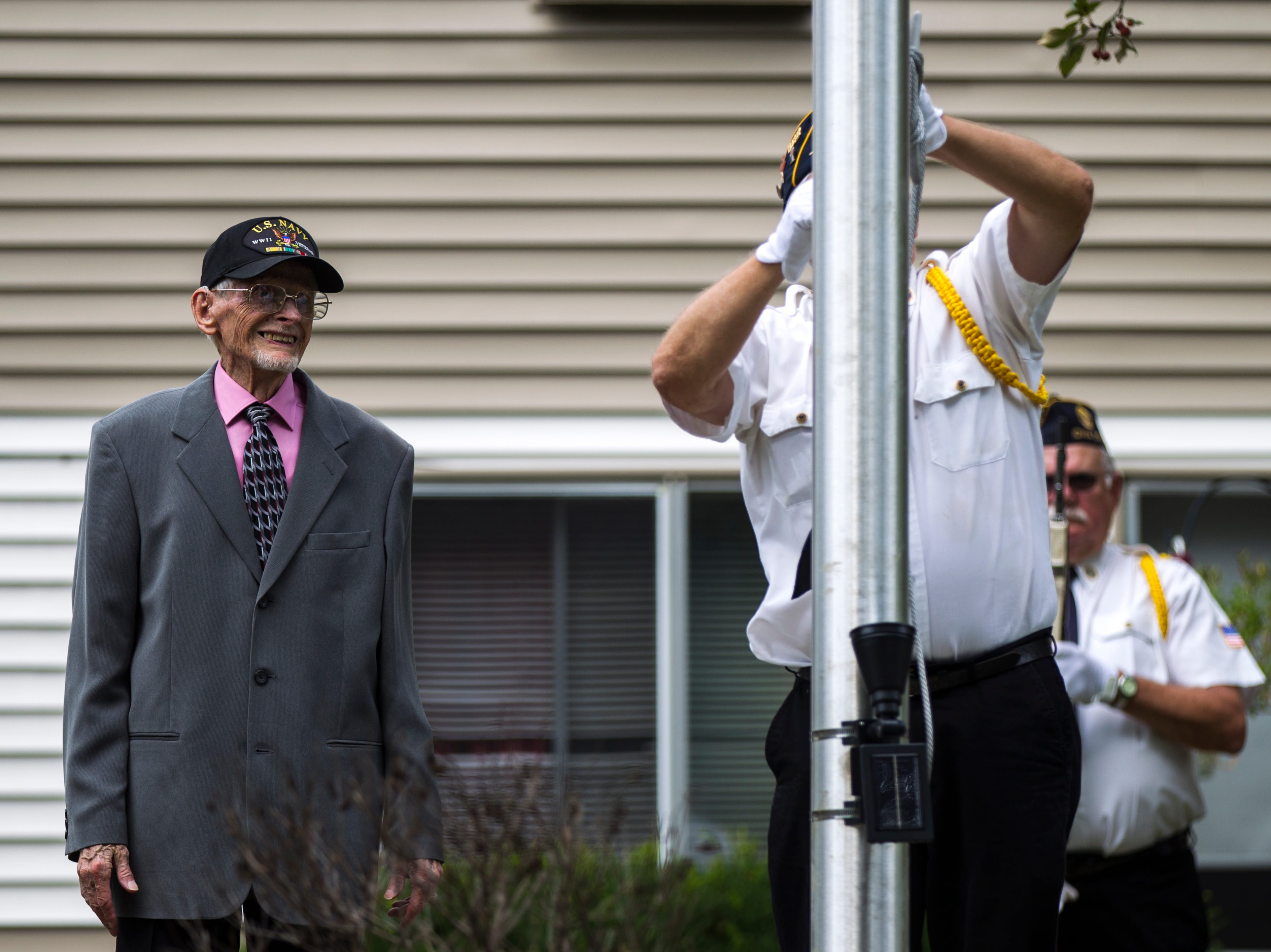 World War II U.S. Navy veteran Russell H. Ware (left) watches American Legion Post 721 honor guard Sgt. of arms Tom Travis raise a flag during a dedication ceremony on Monday, Sept. 3, 2018, at the Autumn Park Apartments in Iowa City.