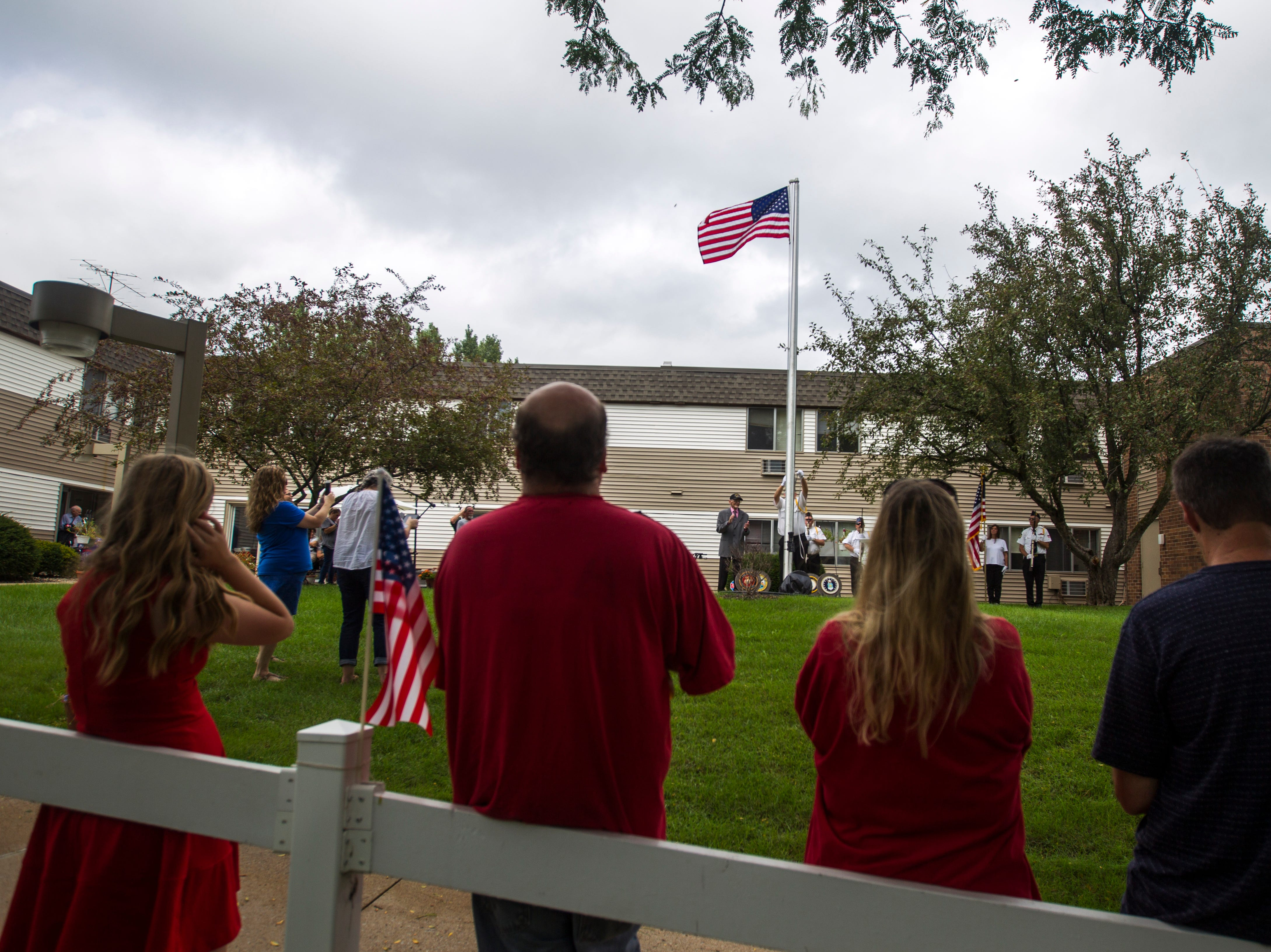 Spectators watch World War II U.S. Navy veteran Russell H. Ware and American Legion Post 721 honor guard Sgt. of arms Tom Travis raise a flag during a dedication ceremony on Monday, Sept. 3, 2018, at the Autumn Park Apartments in Iowa City.