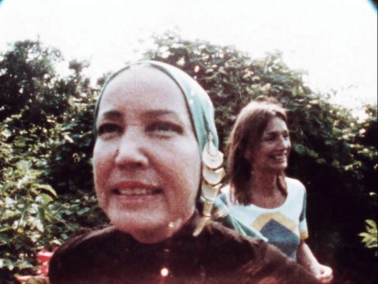 "Little Edie Beale (foreground) sings while Lee Radziwill listens in the garden of Grey Gardens in an image from ""That Summer."""