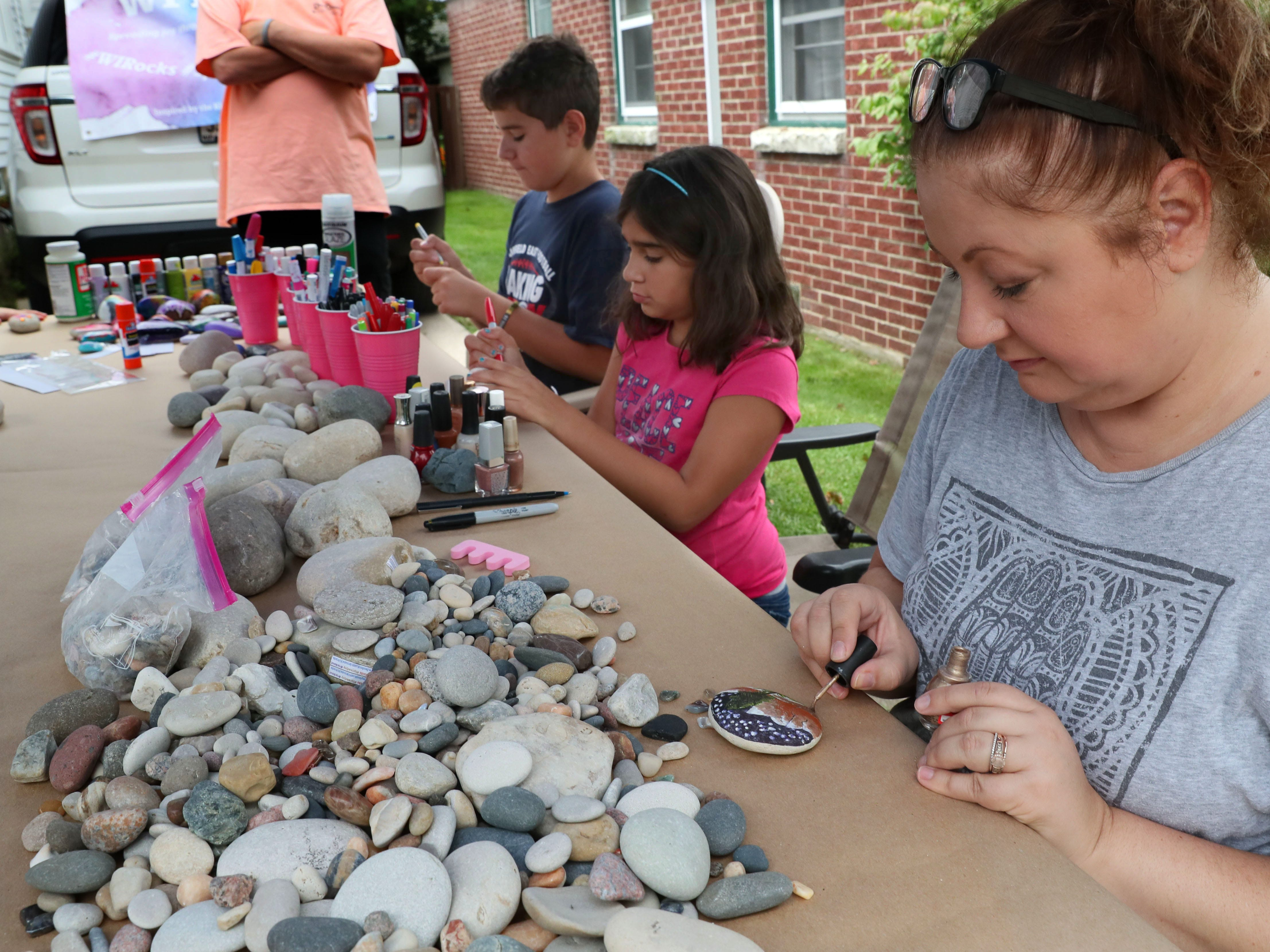 Heather Zunker (from right), Solana Zagorski and her brother, Emilio Zagorski paint rocks for WI Rocks.