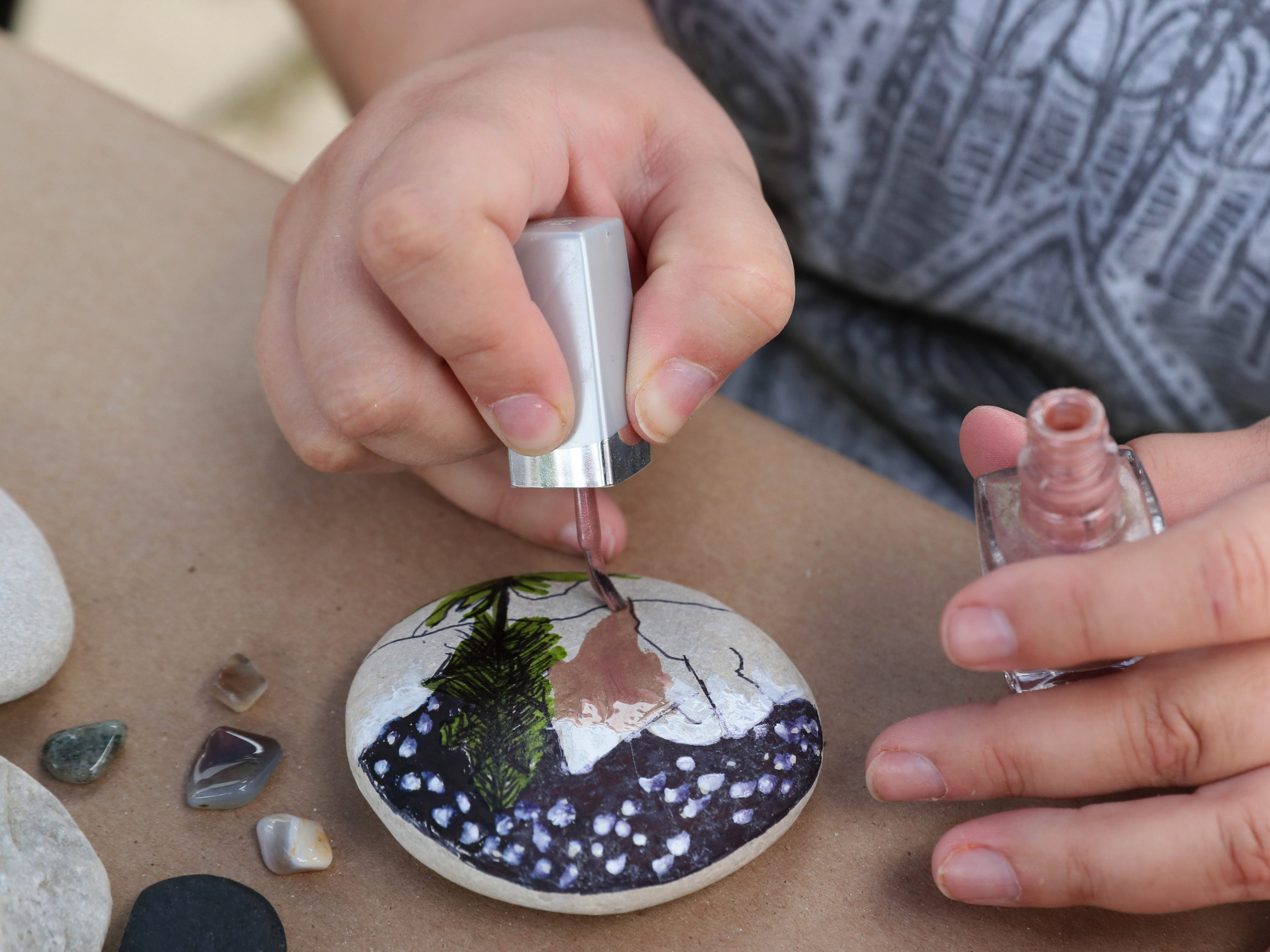Heather Zunker paints a rock, using nail polish.