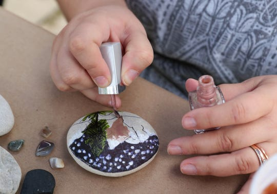 Heather Zunker paints a rock, using nail polish.