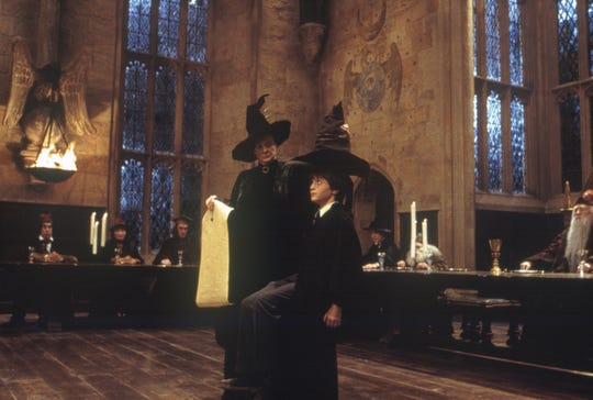 "Harry (Daniel Radcliffe, center) faces the Sorting Hat in ""Harry Potter and the Sorcerer's Stone,"" the first movie in the series."