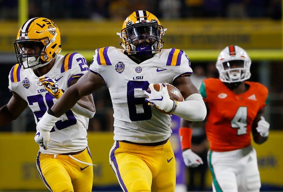 LSU linebacker Jacob Phillips (6) returns an interception for a touchdown as Miami wide receiver Jeff Thomas (4) and LSU cornerback Greedy Williams (29) look on during the first half of an NCAA college football game Sunday, Sept. 2, 2018, in Arlington, Texas. (AP Photo/Ron Jenkins)