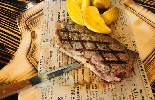 A New York strip steak with gold potato wedges at Western Prime Burger, which recently launched at Mission Square on Pine Ridge Road in North Naples.