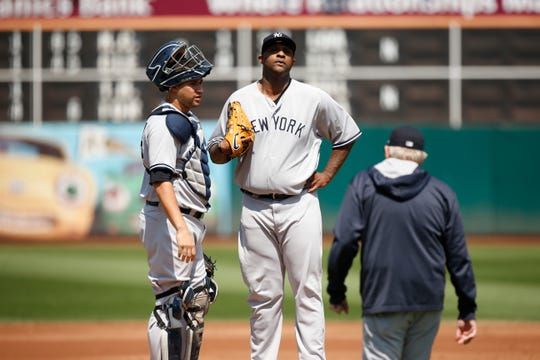 New York Yankees pitcher CC Sabathia (52) stands next to New York Yankees catcher Gary Sanchez (24) after issuing a bases loaded walk against the Oakland Athletics in the first inning at Oakland Coliseum.