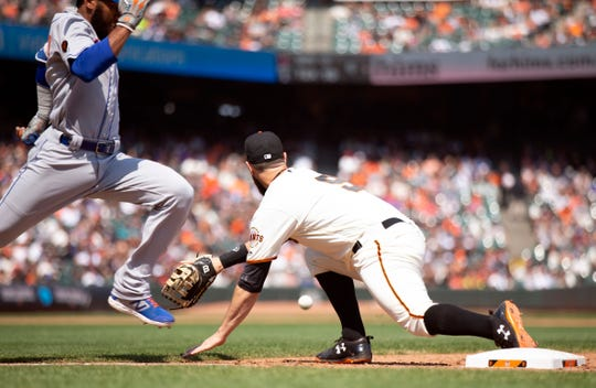 Sep 2, 2018; San Francisco, CA, USA; San Francisco Giants first baseman Brandon Belt (9) stretches to reach the relay from shortstop in time to get New York Mets Amed Rosario (1) during the sixth inning at AT&T Park.
