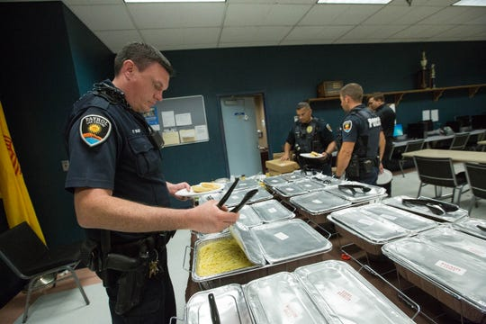 Las Cruces Police Officer Pierce Wilber opens up trays of food donated by Olive Garden to LCPD on Labor Day, Monday Sept. 3, 2018.