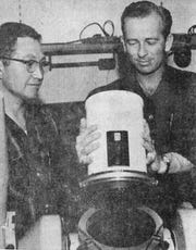 This photo ran in the April 14, 1961 issue of the Wind and Sand newspaper. Optical engineer William Russell, on the right, demonstrates the precision fit between a lens and a cinetheodolite. Placido Trujillo, on the left, and his team, fabricated the interface that made the instrument possible.