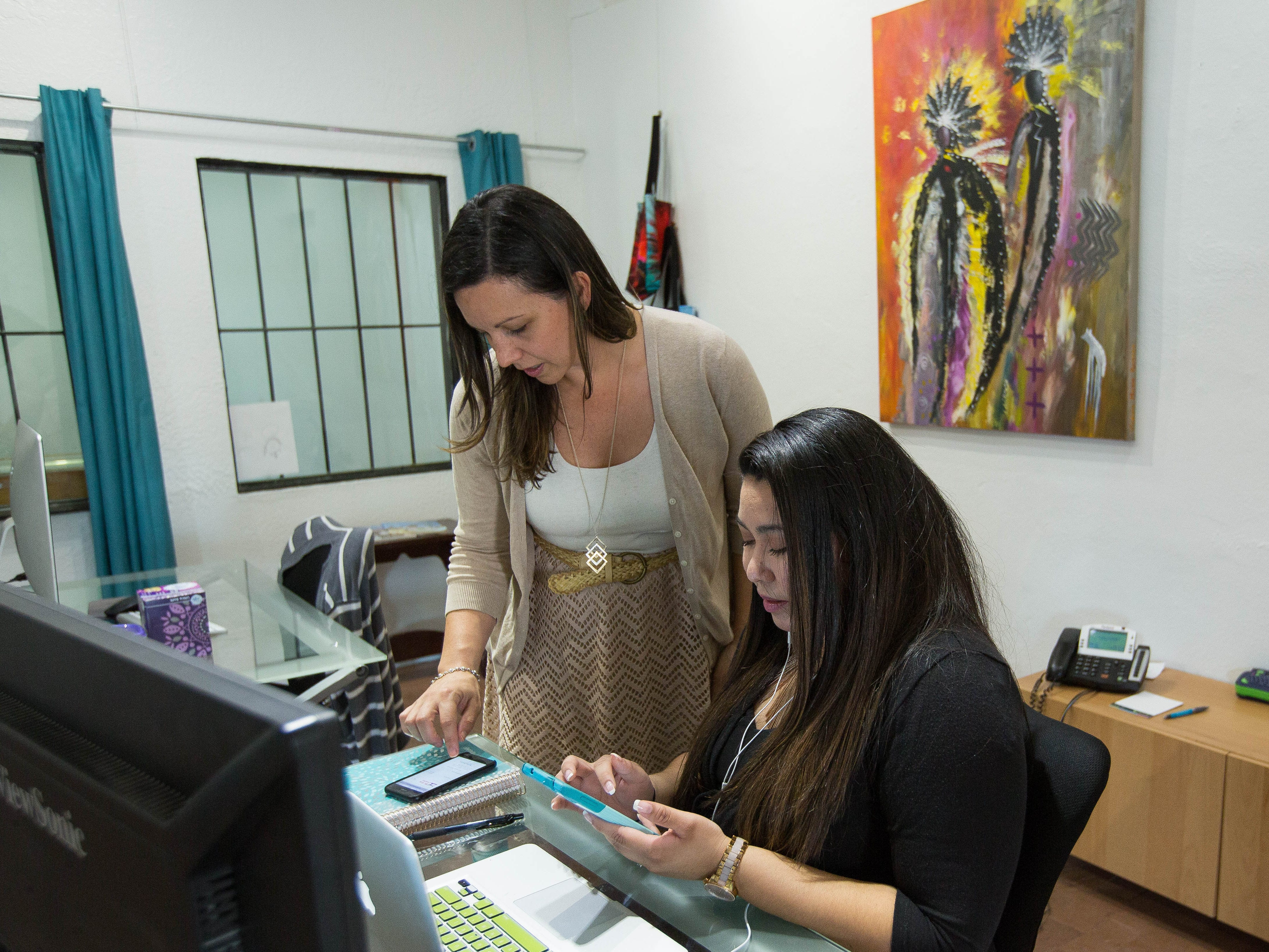 Leah Messina, left, CEO of Sinuate Media, and marketing manager Isabella Pedicone discuss web marketing at the marketing firm's new base of operation in Mesilla on Friday, Aug. 31, 2018.