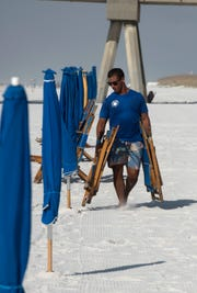 Brian Rodriquez of Lazy Day Beach rentals puts out beach chairs for visitors to Pensacola Beach this Labor Day, Sept. 3, 2018.