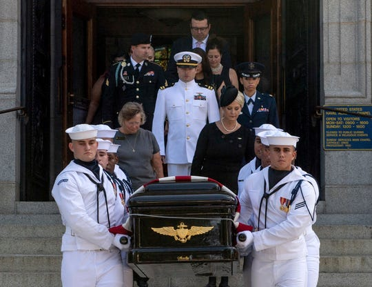 Navy Body Bearers walk with the casket of Sen. John McCain followed by family members including Cindy McCain, to place it onto a horse-drawn caisson after his funeral service at the United States Naval Academy Chapel, Sunday, Sept. 2, 2018, in Annapolis, Md. McCain was buried in the cemetery at the Naval Academy.