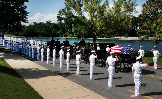 In this photo provided by the family of John McCain, the horse-drawn caisson bearing the body of Sen. John McCain, R-Ariz., moves through the grounds of the United Sates Naval Academy toward the cemetery after a service in the Chapel Sunday, Sept. 2, 2018, in Annapolis, Md. (David Hume Kennerly/McCainFamily via AP)