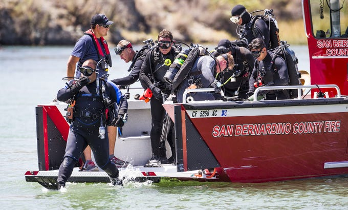 Divers with the San Bernardino County Sheriff's Department enter the Colorado River about 1/2 mile south of the Topoc Marina to search for three people still missing from a boat collision Saturday night about 30 miles north of Lake Havasu City.  Nine people were injured in the crash.