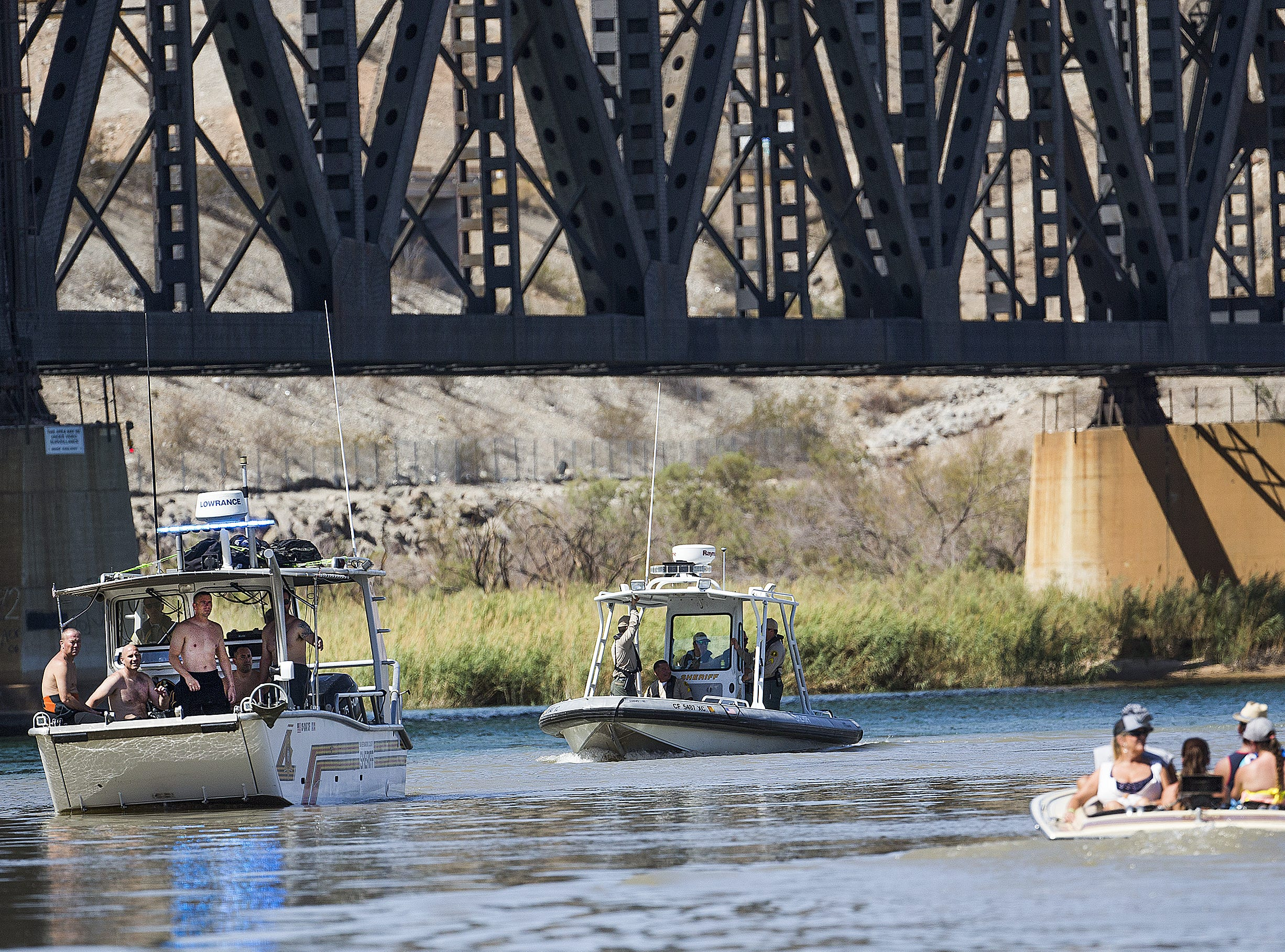 Divers with the San Bernardino County Sheriff's Department are brought back past recreational boaters to the Topoc Marina on the Colorado River while searching for three people still missing from a boat collision Saturday night on the River.  The marina is 30 miles north of Lake Havasu City.  Nine people were injured in the crash.