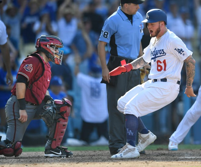 Alex Avila #5 of the Arizona Diamondbacks watches as Alex Verdugo #61 of the Los Angeles Dodgers runs home after being driven in on a double by Matt Kemp to win the game in the nineth inning against the Arizona Diamondbacks at Dodger Stadium on September 2, 2018 in Los Angeles, California.