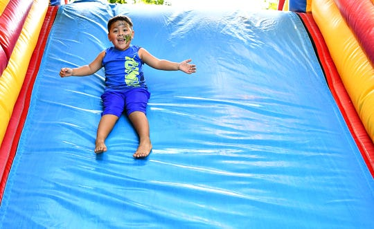 Jose Marin, 4, of York City, glides down the inflatable slide during the Labor Day Festival at Kiwanis Lake in York City, Monday, Sept. 3, 2018. Dawn J. Sagert photo