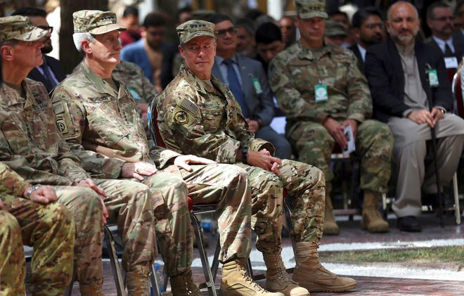 Outgoing U.S. Army Gen. John Nicholson, second from left, listens as incoming U.S. Army Gen. Austin Miller, third from left, looks at him before the change of command ceremony starts at Resolute Support headquarters, in Kabul, Afghanistan, Sunday, Sept. 2, 2018.  Miller has assumed command of the 41-nation NATO mission in Afghanistan following a handover ceremony.   A U.S. service member has been killed and another wounded in an apparent insider attack in eastern Afghanistan.   (AP Photo/Massoud Hossaini)