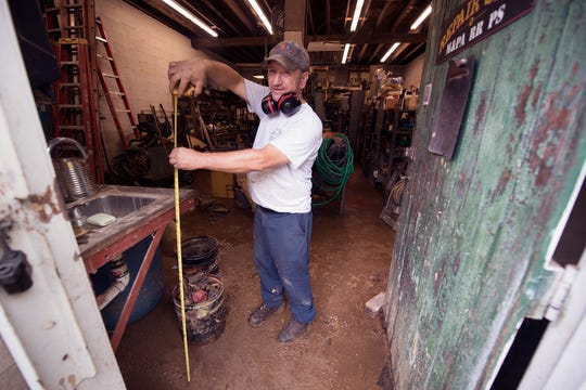 Mike Shay measures a waterline Monday of a little more than three-and-a-half feet of water that was in the Ma & Pa Railroad Heritage Village repair shop in Muddy Creek forks.