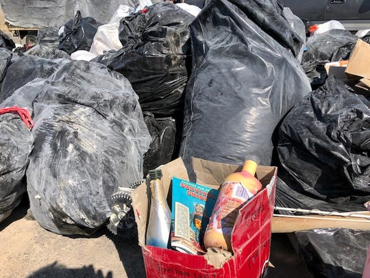 "A Burning Man ""Survival Guide"" sits in a box between two empty booze bottles at a trash collection site  on Highway 447. At mile marker 50, Stephanie Deems set up a trash collection for Burning Man. She'll collect trash for $5 per bag, then sort recyclables, bikes and useful items for reuse."