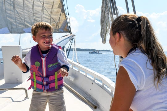 Harvey Whitelock and Logan Lankford play aboard the Kathryn during the 59th annual Deal Island Skipjack Race on Monday, Sept. 3.